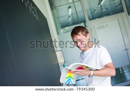 handsome college student solving a math problem during math class in front of the blackboard/chalkboard (color toned image)