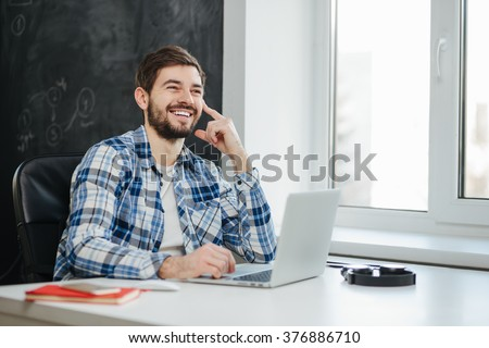 Handsome college student using his laptop computer in the study room - stock photo