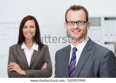 Handsome confident businessman in glasses standing facing the camera with a friendly smile with an attractive female coworker in the background - stock photo