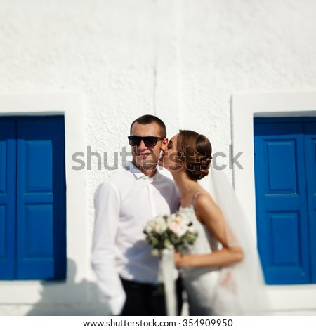 Handsome confident groom and beautiful caucasian bride posing near white wall with blue windows - stock photo