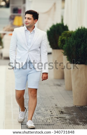 Handsome confident groom in white suit walking near pool at resort - stock photo