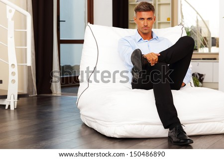 Handsome confident man sitting in armchair at home - stock photo