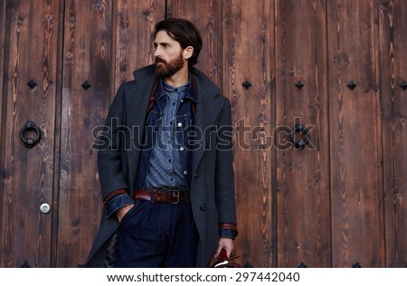 Handsome confident mature man with beard stands on wooden brown background with copy space for your text message or advertising, fashionable rich male dressed in expensive clothes posing outdoors - stock photo