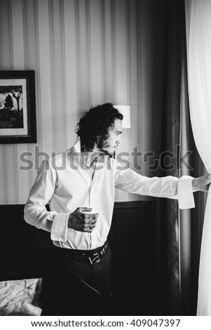 Handsome confident strong man in shirt looking through window b&w