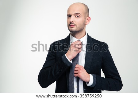 Handsome confident young business man in black suit  straightening his tie over white background - stock photo