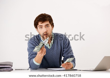 Handsome confident young businessman sitting at the office desk holding stack of cash in his hands and throwing money forward to camera. Looking at camera. Isolated on white background. - stock photo