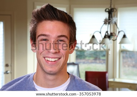 Handsome confident young man relaxing at home looking at the camera - stock photo