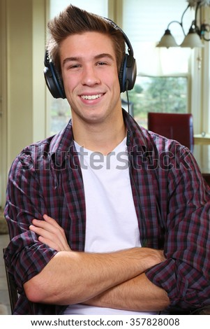 Handsome confident young man relaxing at home looking at the camera with a friendly smile listening to music - stock photo