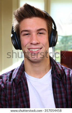 Handsome confident young man relaxing at home looking at the camera with headphones - stock photo