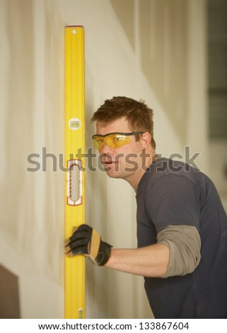 Handsome construction man at work checking new wall - stock photo