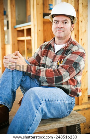 Handsome construction worker sitting down for a rest, with a serious expression.   - stock photo