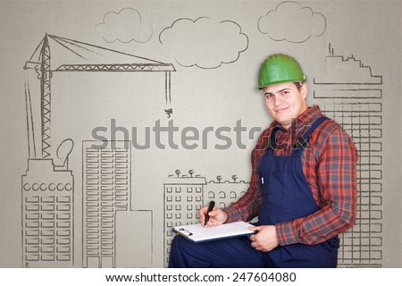 Handsome construction worker specialist (architect) planing something on building operation drawn background - stock photo