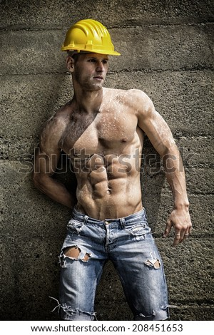 Handsome construction worker standing shirtless in front of a concrete wall
