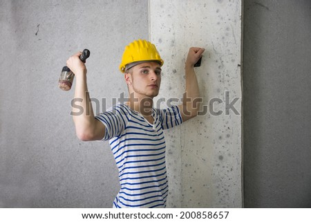 Handsome construction worker with yellow hard hat and hammer in hand