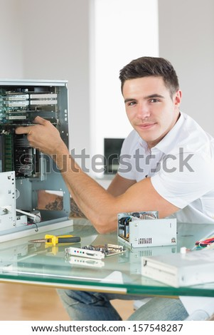 Handsome content computer engineer working at open computer in bright office