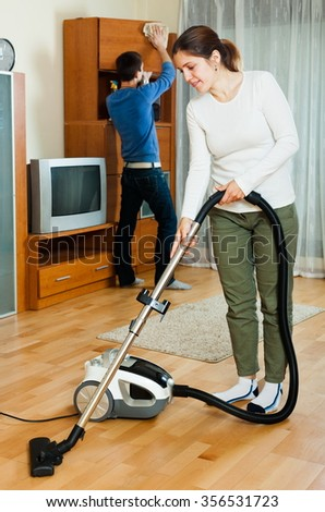 Handsome couple doing housework together in home