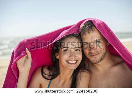 handsome couple on the seaside sheltering under a beach towel - stock photo