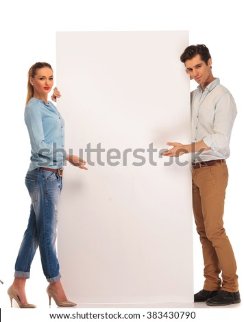 handsome couple posing in isolated studio background while presenting a white blank billboard and looking at the camera  - stock photo