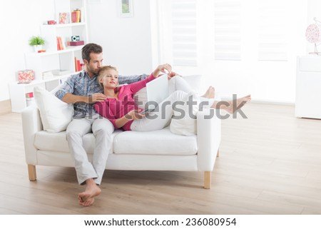 Handsome couple relaxing barefoot on a white sofa and using laptop - stock photo