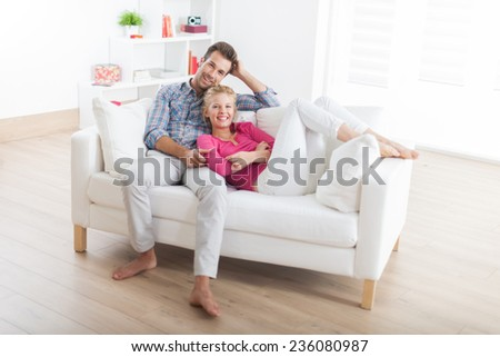 handsome couple relaxing barefoot on a white sofa in their modern living room