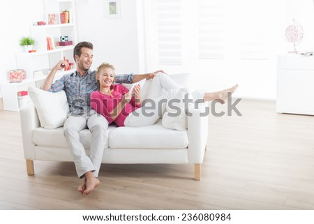 Handsome couple relaxing on a white sofa and using a digital tablet - stock photo
