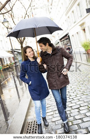 Handsome couple under the rain on street in Paris