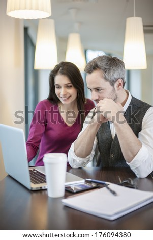 handsome couple using a laptop in a cafe - stock photo