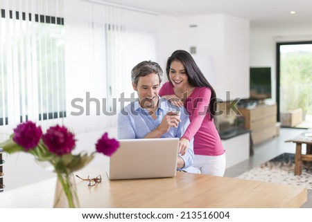 handsome couple using laptop at home - stock photo