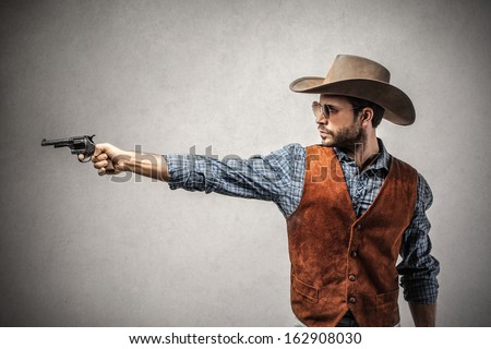 handsome cowboy with a gun - stock photo