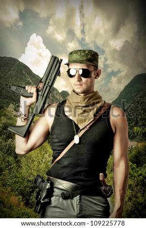 Handsome dangerous military man holding automatic and gun wearing fashion sun glasses - stock photo