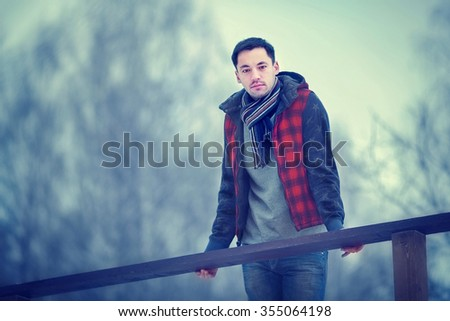 Handsome dark-haired young man in red waist coat walking in a winter park. Image with selective focus and toning - stock photo