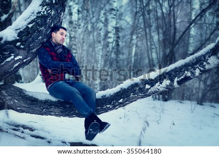 Handsome dark-haired young man sitting on the birch and musing upon a distant scene in a snow-covered park. Image with selective focus and toning - stock photo