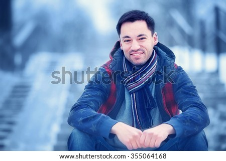 Handsome dark-haired young man sitting on the stairs in a snow-covered park. Image with selective focus and toning - stock photo