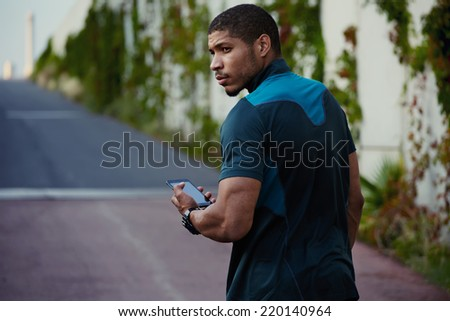 Handsome dark skinned jogger relaxing after workout outdoors, beautiful muscular body man using his mobile phone walking on the road, afro american jogger taking break using  phone standing outdoors - stock photo