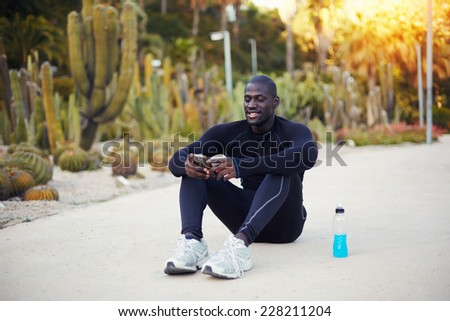 Handsome dark skinned jogger relaxing after workout outdoors, beautiful sportsman using his mobile phone sitting on the road, afro american jogger taking break using phone seated outdoors - stock photo
