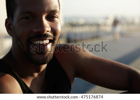Handsome dark-skinned jogger resting at seaside after outdoor training sitting on pavement thinking about his future plans and goals. Happy black student enjoying his summer vacation in city