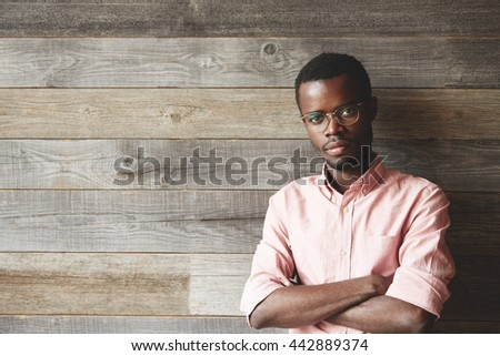 Handsome dark-skinned young man wearing glasses and pink shirt, looking at the camera with serious confident expression, standing against wooden wall with copy space for your promotional content - stock photo
