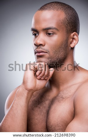 Handsome day dreamer. Portrait of young African man holding hand on chin and looking away while standing against black background - stock photo
