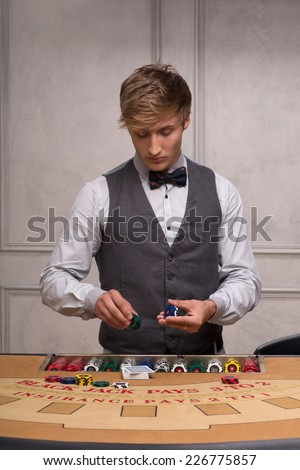 Handsome  dealer  recounting  chips near table with  red blue and white chips in piles in casino