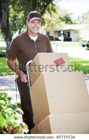 Handsome delivery man or mover pushing a stack of boxes on a dolly, outdoors. - stock photo