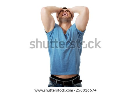 Handsome depressed man with hands behind head. - stock photo