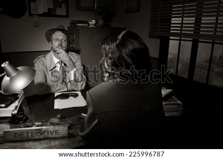 Handsome detective at office desk interviewing a young woman, 1950s film noir style.