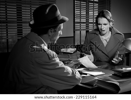 Handsome detective at office desk showing a picture to a young woman, film noir scene. - stock photo