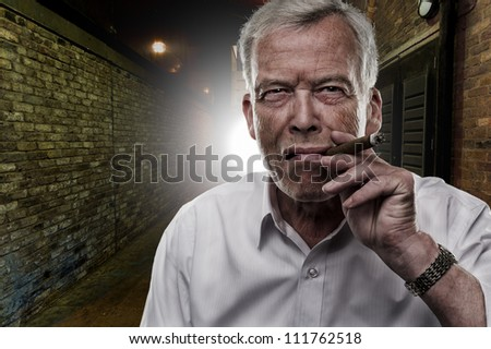 Handsome determined senior man smoking a cigar outdoors in the darkness backlit by a light on a brick building - stock photo