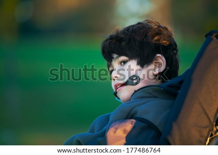 Handsome disabled boy sitting quietly in wheelchair at park, looking to side - stock photo