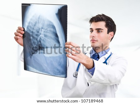 Handsome doctor examining a radiography - stock photo