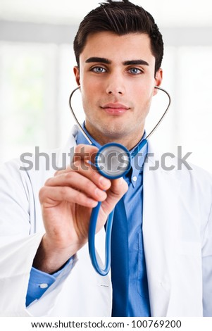 Handsome doctor holding a stethoscope - stock photo