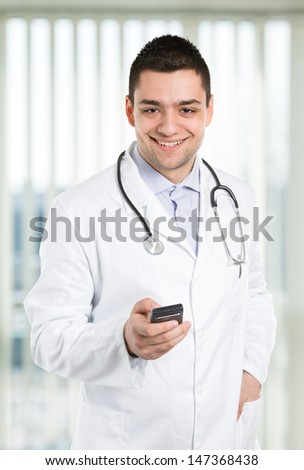 Handsome doctor holding cell phone at the office.
