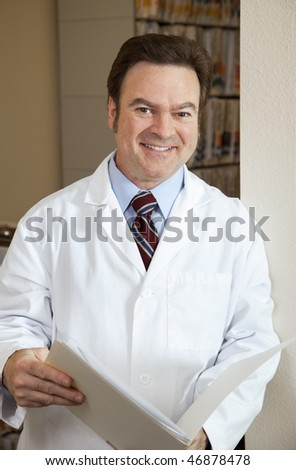 Handsome doctor in his filing room reviewing a chart.