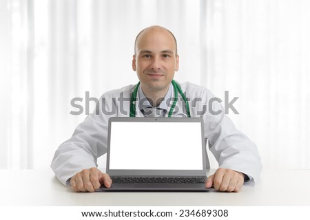 handsome doctor sitting at a desk with laptop computer - stock photo
